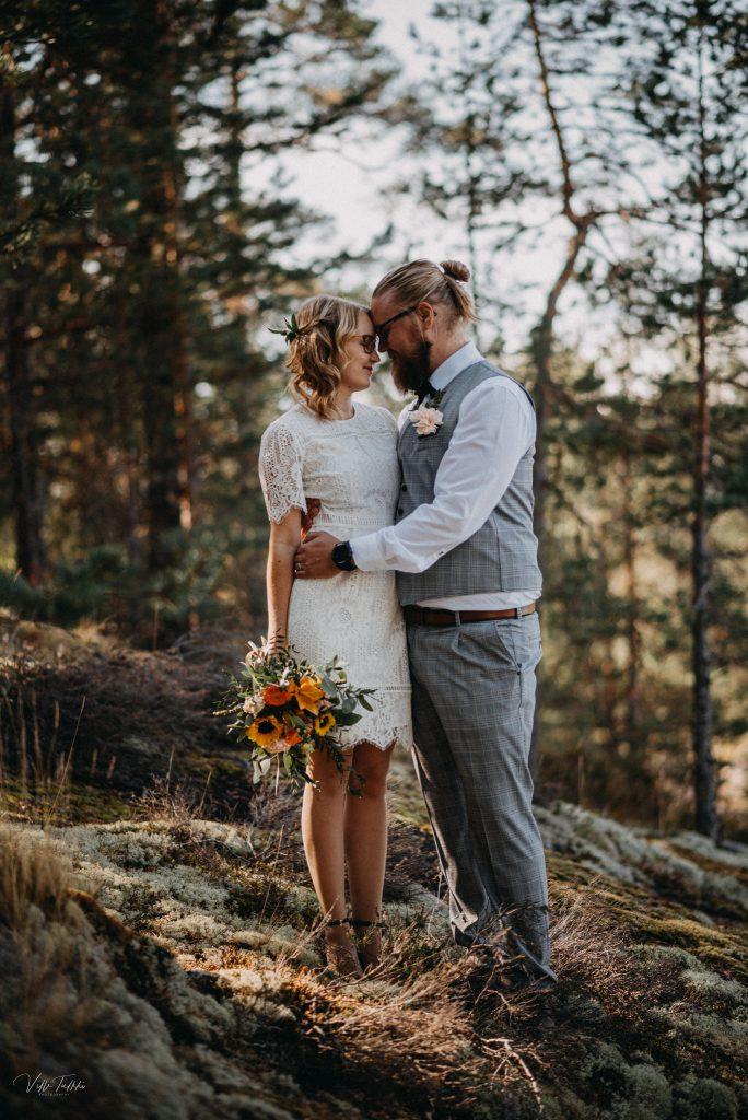 Hääkuva Taipalsaari, hääpari aamuauringossa sammaleen peittämällä kalliolla pienessä metsikössä.