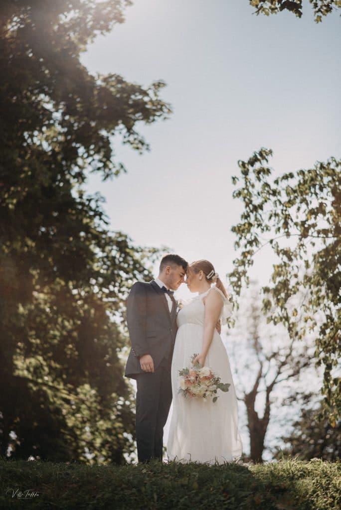 Pariskunta hääkuvassa lappeenrannan linnoituksen päällä, taustalla epäterävänä puustoa ja aurinko.