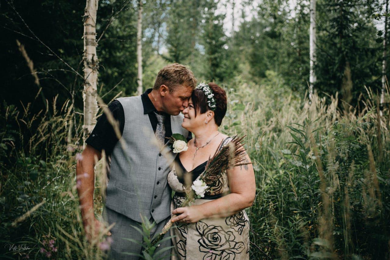 Pariskunta metsässä/ruohikossa.