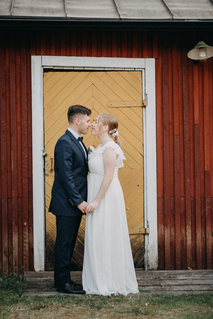Pariskunta hääkuvassa lappeenrannan linnoituksella, taustalla taustalla majurkan takana olevan rakennuksen ovi.