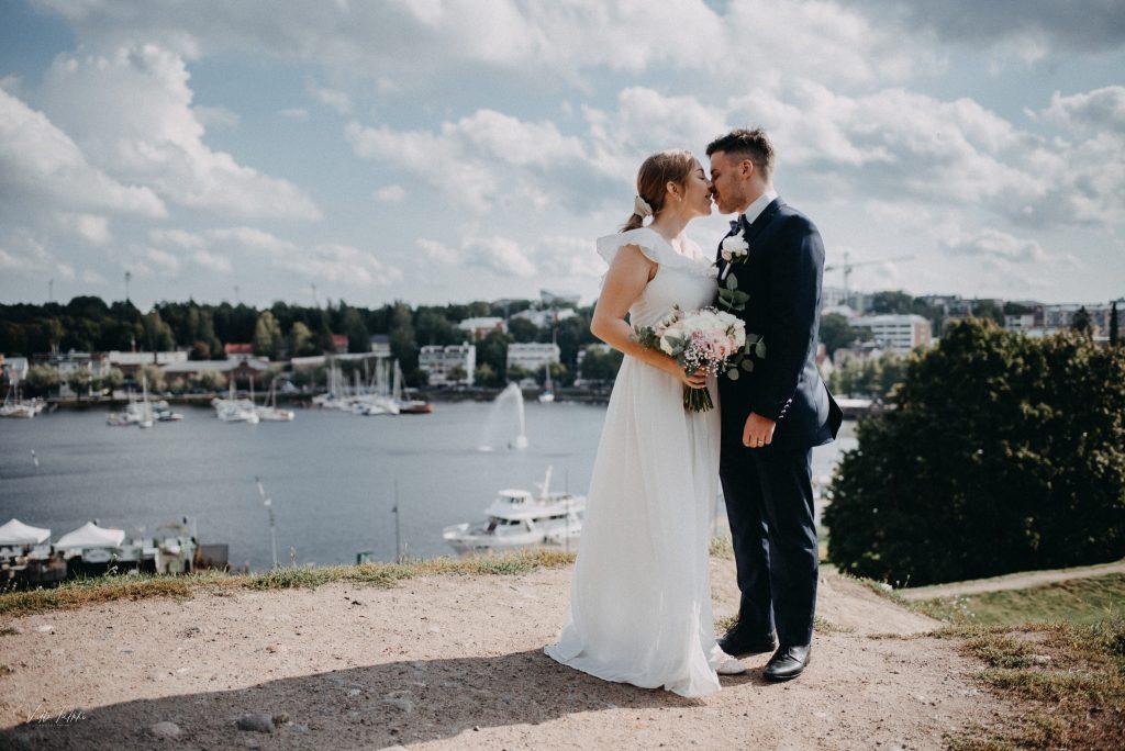 Pariskunta hääkuvassa lappeenrannan linnoituksen päällä, taustalla satama ja suihkulähde.