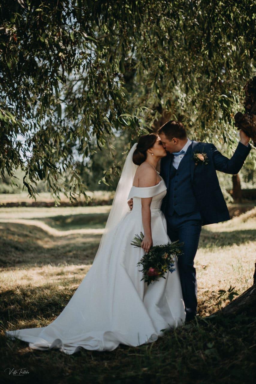Hääpari suutelee puun varjossa